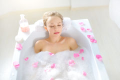 Attractive girl relaxing in bath on light background Royalty Free Stock Image