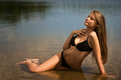 Attractive girl relaxing by the river Royalty Free Stock Image