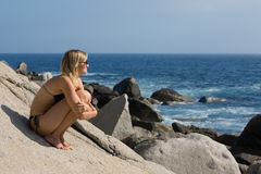 Attractive girl relaxing rocky beach by the sea. Royalty Free Stock Photography