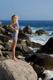 Attractive girl relaxing rocky beach by the sea. Royalty Free Stock Images
