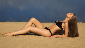 Attractive girl relaxing on a sandy beach Stock Image