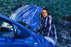 attractive girl repairs car on road stock photos