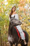 Attractive girl riding a horse against a background of autumn foliage. Royalty Free Stock Photography