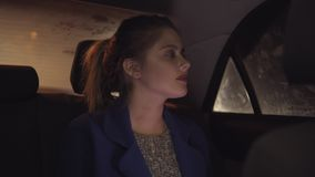 Attractive girl riding in a taxi at night sitting on the backseat and moving her head listening to the music. Happy. Woman in taxi. Night live. Slowmotion shot stock video footage
