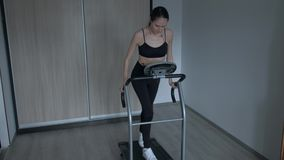 Attractive girl running at home on a treadmill. Female in black tracksuit for Jogging and white sneakers is engaged in sports at home stock video footage