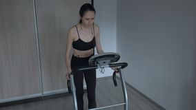 Attractive girl running at home on a treadmill. Listens to music in the player wearing headphones. Female in black tracksuit for Jogging and white sneakers is stock video