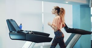 Attractive girl running on the treadmill in the sport gym. Attractive curly girl running on the treadmill in the sport gym 4K stock footage