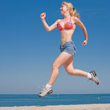 Attractive girl runs. Vigorous blond woman in shorts and top of swimsuit is running outdoors Stock Photos