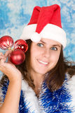 Attractive girl in santa cloth with holiday balls. Royalty Free Stock Photos