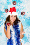 Attractive girl in santa cloth juggling with holid Stock Photography