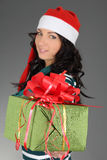 Attractive girl in santa hat with gift Stock Images