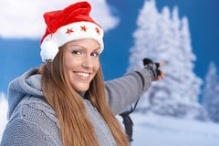 Attractive girl in santa hat pointing to landscape Stock Image