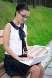 Attractive girl in school uniform using laptop in park or campus Royalty Free Stock Images