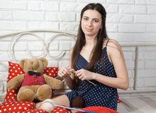 Attractive girl seamstress engaged in knitting on a bed Royalty Free Stock Image