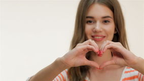 Attractive girl showing heart shape gesture stock video footage