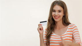 Attractive girl showing thumbs-up with credit card