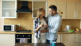 Attractive girl shows pregnancy test result to her boyfriend and surpise him at the kitchen stock photos