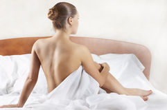 Attractive girl sits on beds (type behind) Royalty Free Stock Images