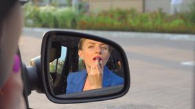 Attractive girl sits in car and uses lipstick. She does makeup for her lips. Girl looks in the mirror. stock footage