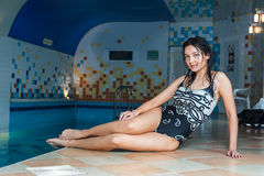Attractive girl sits on swimming pool side Stock Images