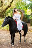 An attractive girl is sitting on a black horse. Outdoors. Stock Photos