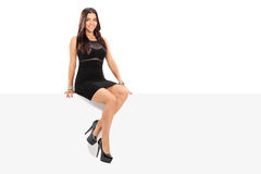 Attractive girl sitting on a blank panel Stock Photography