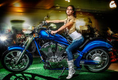 Attractive girl sitting on a blue motorcycle, moto show. Beautiful fashionable brunette woman posing on a blue motorcycle. Indoors, blurred background Stock Photo