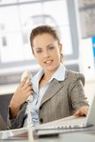 Attractive girl sitting by desk in bright office Royalty Free Stock Image