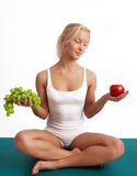 Attractive girl sitting on mat with fruits Stock Photos