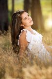 Attractive girl sitting in meadow with white dress Stock Photography