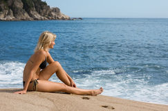 Attractive girl sitting on the sand beside the sea Stock Image