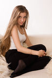 Attractive girl sitting on a sofa. Attractive blonde girl sitting on a sofa Royalty Free Stock Photography