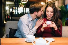 Attractive girl is sitting on the sofa in restaurant and drinking some tea while her partner has put his hand over her. Shoulder and looking to her. She is royalty free stock image