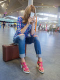 Attractive girl sitting on a suitcase in the airport hall. Fatigue. From expectations. Suitcase brown  in retro style Royalty Free Stock Photo