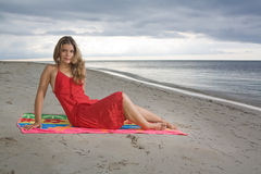 Attractive girl sitting on a towel, with red dress Royalty Free Stock Photography