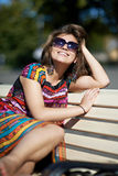 Attractive girl sitting on wooden bench Stock Photo