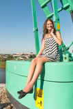 Attractive girl smiles on construction crane Royalty Free Stock Images