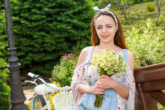 Attractive girl smiling with flowers standing near bike. Single attractive girl smiling and holding large bouquet of little white flowers while leaning on Stock Images