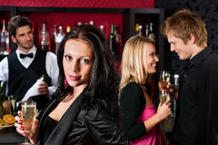 Attractive girl smiling with friends at bar Stock Photos