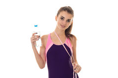 Attractive girl sports swimsuit looks straight and holding a water bottle isolated on white background Royalty Free Stock Photo