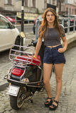 Attractive  girl standing in the european town near his motorbike. Royalty Free Stock Photo