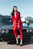 Attractive girl standing next to a retro sport car on the sun. Fashion woman in a red suit and sunglasses waiting near classic car. Mafia lady outside japonese Royalty Free Stock Photography