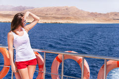 Attractive girl is standing and relaxing on a yacht. Stock Photography