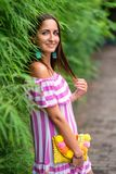 An attractive woman in a striped dress and a handbag in her hands leaned against a green fence.  stock photography
