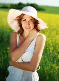 Attractive girl in a summer hat on a green glade Royalty Free Stock Photos