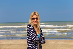 Attractive girl in sunglasses on the beach. Spring Royalty Free Stock Photo