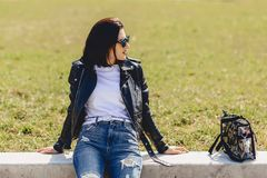 Attractive girl in sunglasses on grass in park. Attractive young girl in sunglasses on grass in park Royalty Free Stock Photo