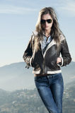 Attractive girl with sunglasses and leather jacket. On top of a hill Royalty Free Stock Photos