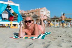Attractive Girl in Sunglasses Lies on Warm Sand Royalty Free Stock Photo