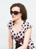 Attractive girl in sunglasses. And a polka dot dress Stock Image